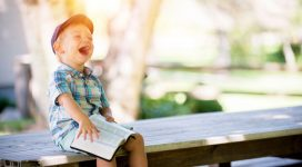 bimbo con libro che ride - leggiamo insieme al giardino della salute